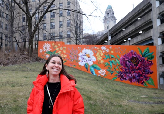 """Brooklyn artist Surface of Beauty (Natasha May Platt) is pictured in front of her new public art mural called """"Orange Joy"""", that's painted on the side of the Government Center Garage on New Main Street in Yonkers, Jan. 7, 2020. The new mural joins dozens of public art pieces displayed throughout the Yonkers downtown. This 900 square foot mural commissioned by the city, features several wildflowers native to the region. It is designed as a focal point of healing and joy for the community with larger than life blossoming flowers."""