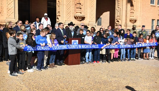 Mayor Stephen Santellana prepares to cut a ribbon kicking off the Official 2020 Census for Wichita Falls Tuesday with the help of numerous WFISD fourth graders, city officials and community leaders.