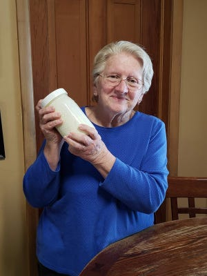 Susan shakes the jar of heavy cream.