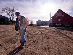 In this Friday, Dec. 27, 2019 photo, farmer Kurt Kaser walks across a yard at his farm in rural Pender, Neb. In April, Kaser's left leg was partially amputated after stepping into a running grain auger and he used his pocket knife to sever the remaining tissue before crawling to his home to call for help. Since the accident, he is on his second prosthetic leg and has traveled to Germany to appear on a television show.