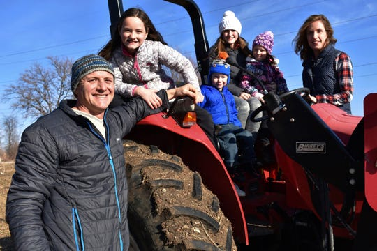 In this Dec. 21, 2019, photo, Adam Aberle, from left to right, Ava Aberle, Andrew Aberle, Kaylee Aberle and wife Kristina gather for a family photo on a tractor in Beloit, Wis. The family is farming hemp together.