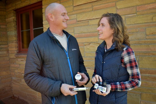 In this Dec. 21, 2019, photo, Adam Aberle and wife Kristina Aberle hold CBD oil, as well as other CBD infused products they sell, in this photo in Beloit, Wis. Aberle jokes that his family hemps together.