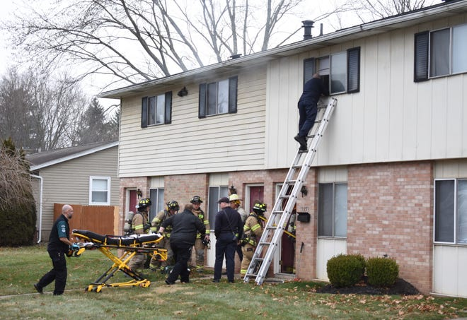 Zanesville Fire Department and Genesis Community Ambulance personnel work to ventilate the apartment and remove the woman from the apartment on Fairway Lane after a fire broke out upstairs Tuesday morning.