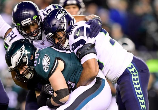 Dallas Goedert #88 of the Philadelphia Eagles is tackled by K.J. Wright #50 and Bobby Wagner #54 of the Seattle Seahawks during the NFC Wild Card Playoff game at Lincoln Financial Field on January 05, 2020 in Philadelphia, Pennsylvania.