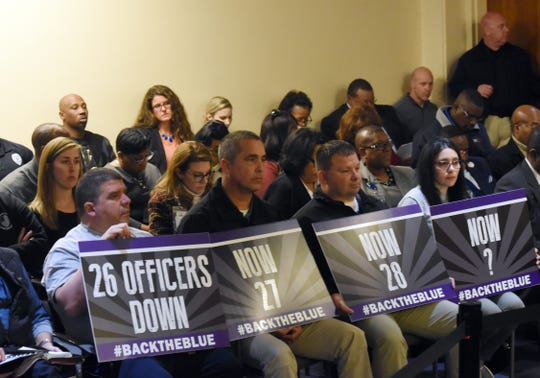 Supporters of Alexandria Police Chief Jerrod King hold signs at the City Council meeting Jan. 7.