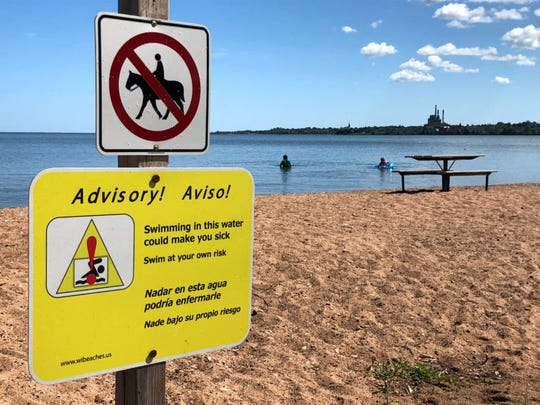 A sign warns of the risks of swimming at Lake Superior's Maslowski Beach in Ashland, Wis., on Aug. 10, 2019. Researchers have flagged high levels of E. coli at the beach and others along Wisconsin's Great Lakes shoreline. The bacteria arrive in human, bird and animal feces, and can sicken people who ingest them. Researchers worry climate change-induced sewage overflows will only send more pollution into waterways. Such discharges are a prime source for the pathogens most likely to cause illness.