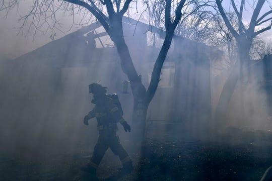 An Abilene firefighter walks past 3909 Chris Dr. which burned Wednesday.