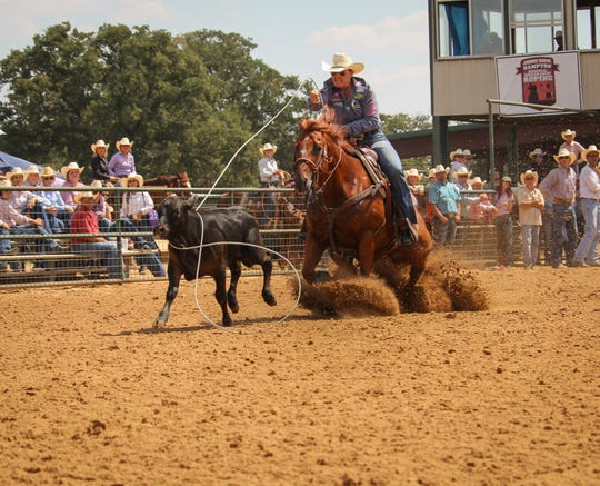 Lari Dee Guy tosses her rope around the neck of a calf at a recent competition. She is an eight-time world champion, and will be inducted next week into the Texas Cowboy Hall of Fame.