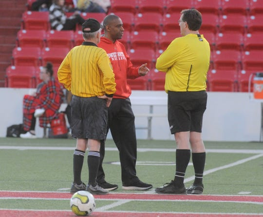 Sweetwater boys soccer coach John Reddic speaks with officials during halftime of the Mustangs' inaugural game against Lubbock Coronado on Tuesday.