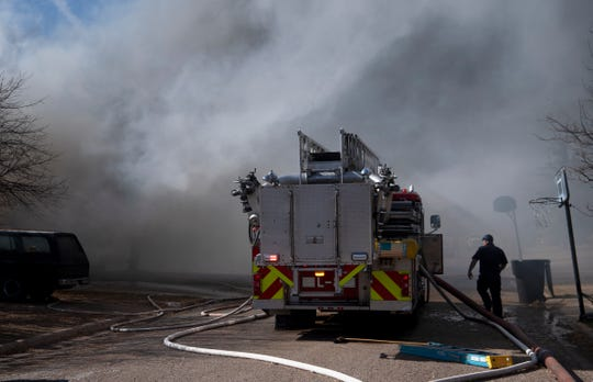 Smoke from two burning homes drifts over an Abilene Fire Department engine as firefighters fight a two-alarm blaze in south Abilene on Wednesday.
