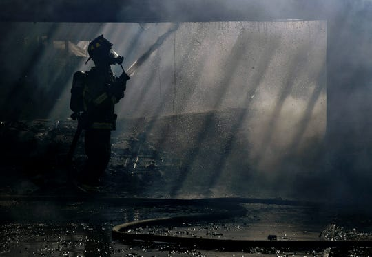 Water is sprayed onto smoldering joists inside the garage at 3909 Chris Drive on Wednesday. Abilene firefighters battled high winds as the two-alarm fire consumed the home and part of a house next door at 3917 Chris Drive.