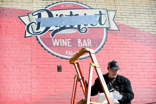 "Barrett Nichols comes down from a tall ladder after covering the word ""District"" in duct tape on the painted mural above the entrance to his family's wine bar in the River Arts District on Jan. 8, 2020. In a trademark dispute, owners of the wine bar are being forced to rebrand by the Mandara Hospitality Group who own District 42 in the Arras hotel. The wine bar will now be called Bottle Riot."
