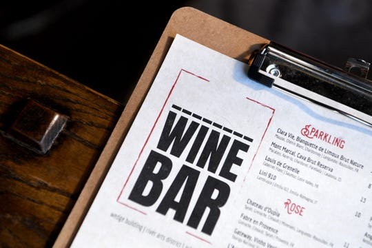"A temporary menu has dashes where the word ""District"" once was at District Wine Bar in the River Arts District following a trademark dispute with the Mandara Hospitality Group. The wine bar is changing their name to Bottle Riot."