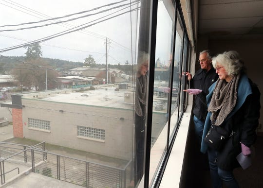 Priscilla Zimmerman and Tom Haggar look at the courtyard below from the second story of the old Virginia Mason clinic on Bainbridge Island's Winslow Way during a tour of the site, which is currently being renovated.