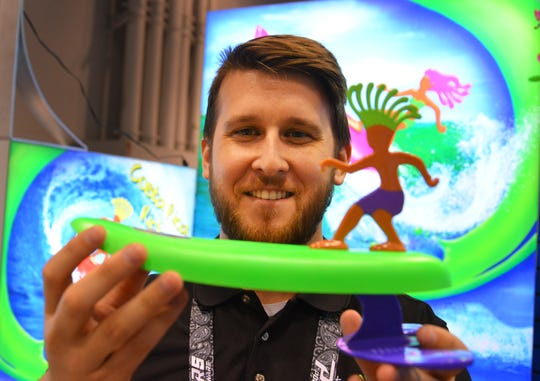 Jordan Reardon, COO of Surfer Dudes in Orlando, shows off a wave-riding toy at the Surf Expo in Orlando.