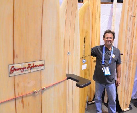 George Robinson of Melbourne shows off his line of custom balsa boards he has made for 50 years. He is standing next to the one he shaped at the first Surf Expo in 1976.