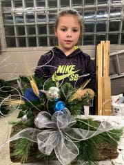Brynn Crall has just finished decorating a Yule Log. This activity was managed when junior gardeners met  before Christmas. Brynn is a member of the Peas- in-a-Pod Club.