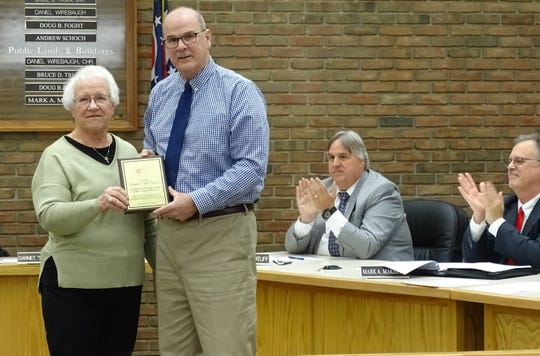 Retiring Council President Sis Love, left, is presented a plaque by Mayor Jeff Reser at her final city council meeting  on Tuesday.