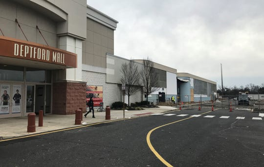 A shopper leaves Deptford Mall where workers are preparing for the arrival of new tenants at a former Sears store.