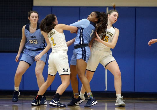 SUA guard Colleen Lekowski and MND guard Makira Cook battle for a rebound in the Girls basketball game between the Saint Ursula Bulldogs and Mount Notre Dame Cougars at Saint Ursula Academy January 07, 2020.