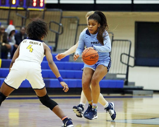 Mount Notre Dame guard Makira Cook attempts to get past St. Ursula Academy guard Shamia Strayhorn in their basketball game Jan. 7, 2020.
