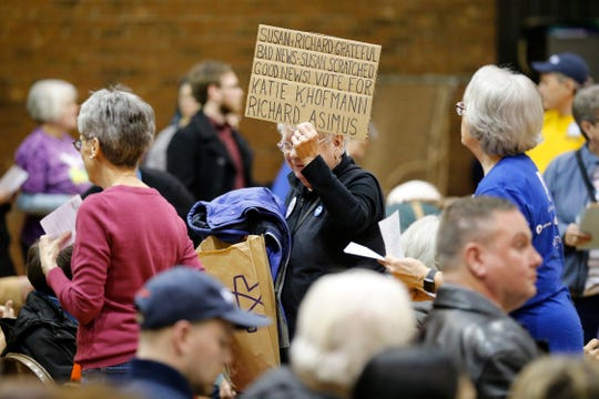 Susan Namei carries a sign during a caucus to elect democratic convention delegates at Winton Woods Intermediate School in Cincinnati on Tuesday, Jan. 7, 2020. Democrats from the 1st Congressional District cast votes for delegates they hope to represent them in the upcoming election.