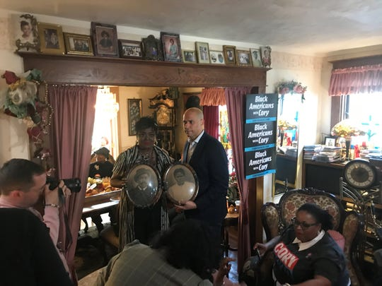 Sen. Cory Booker and his cousin Lizz Sharp pose with photos of Booker's great-great grandparents at Sharp's home on Tuesday afternoon.