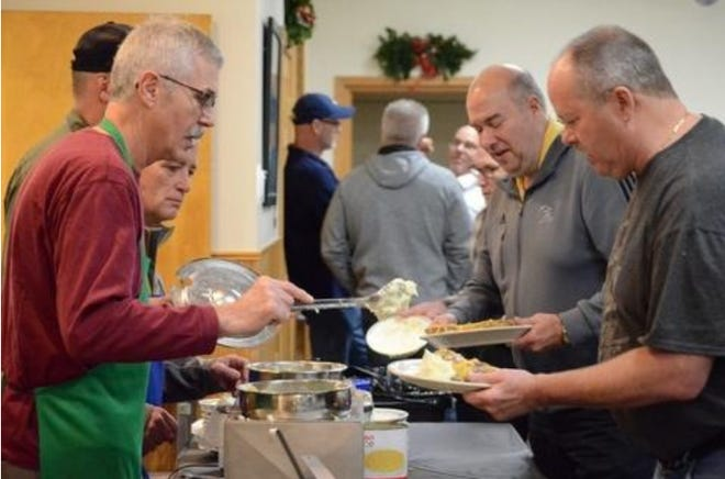 Left: Doug Petee serves up a helping of mashed potatoes to Bob Halstead of Monroe during the Monroe Boat Club's annual muskrat dinner.