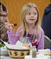 Olivia Fowler, 7, of Monroe, enjoys a forkful of muskrat meat during the Monroe Boat Club's annual muskrat dinner Monday night.