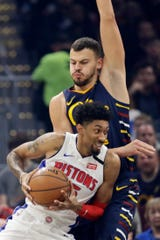 Detroit Pistons' Christian Wood, front, drives past Cleveland Cavaliers' Ante Zizic in the first half of an NBA basketball game, Tuesday, Jan. 7, 2020, in Cleveland.