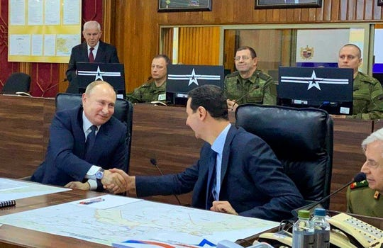 This image released by the Syrian Presidency shows Russian President Vladimir Putin, left, meeting with Syrian President Bashar Assad, center, in Damascus, Syria on Tuesday, Jan. 7, 2020.