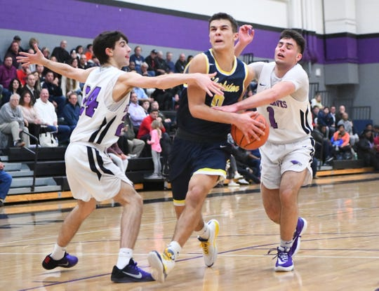 Clarkston's Keegan Wasilk attacks the basket between Bloomfield Hills' Noah Adamczyk and Mason Canfield.
