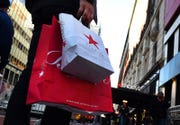 In this November 20, 2015 file photo, shoppers are seen outside Macy's Herald Square in midtown Manhattan. Macy's is closing nearly 30 stores in coming weeks, though they reported some improvement in comparable-stores sales during the holiday season.