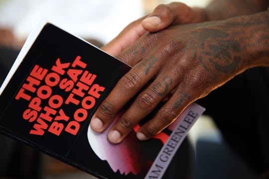 "DeRon Cash holds onto a copy of ""The Spook Who Sat By The Door,"" by Sam Greenlee, during a book club gathering for black men in Los Angeles."