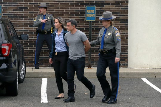Connecticut State Police officers lead Fotis Dulos, center, from the State Police barracks to a waiting car Tuesday, Jan. 7, 2020, in Bridgeport, Conn., after he was arrested at his home in Farmington.