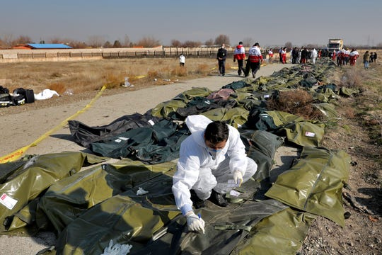 A forensic investigator works at the scene of a Ukrainian plane crash as bodies of the victims are collected, in Shahedshahr, southwest of the capital Tehran, Iran, Wednesday, Jan. 8, 2020.