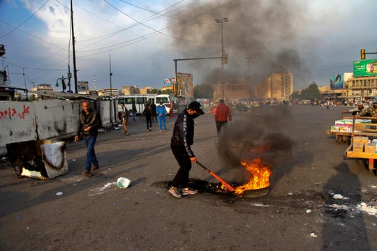 A protester sets fire to close streets near Tahrir Square during a demonstration to protest against the Iranian missile strike, in Baghdad, Iraq, Wednesday, Jan. 8, 2020.