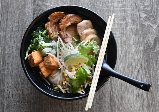 Ramen bowl with pork belly, pork loin, tofu, soft egg in chicken broth.