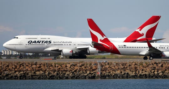 FILE - In this Aug. 20, 2015 file photo, two Qantas planes taxi on the runway at Sydney Airport in Sydney, Australia.