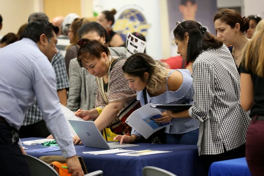 Job applicants looks at jobs available at Florida International University during a job fair in Miami.