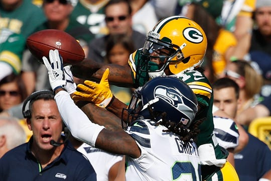 Davante Adams of the Green Bay Packers attempts to make a reception against Shaquill Griffin of the Seattle Seahawks during a 2017 game at Lambeau Field.