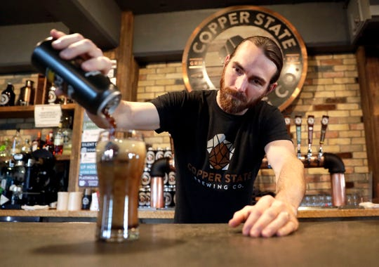 Jonathan Martens, co-owner of Copper State Brewing Co., pours a can of Chocolate Peanut Butter Nitro Porter into a glass on Jan. 8, 2020, at the downtown Green Bay brewery and restaurant.