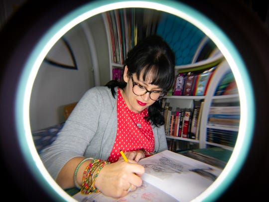 Hallie Bertling as seen through the magnifying light she uses to help her draw sketches at her home studio in Greenville.