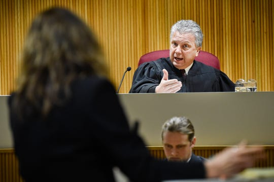 Montana Supreme Court Justice Dirk Sandefur, right, questions Maureen Lennon, attorney for the Montana Association of Counties, arguing on behalf of the Lincoln County Sheriff, on Wednesday in Helena, Mont.,cord via AP)