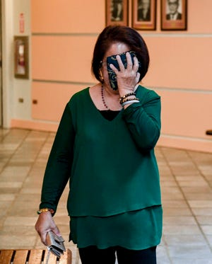 Defendant Yolanda Digomon covers her face as she prepares to enter the courtroom her change of plea hearing before Superior Court of Guam Judge Maria Cenzon at the Guam Judicial Center in Hagåtña on Wednesday, Jan. 8, 2020. During the hearing, Digomon pleaded guilty to unlawfully using, transferring or receiving food stamps and fraudulently using public assistance while working as a government employee with the Supplemental Nutrition Assistance Program.