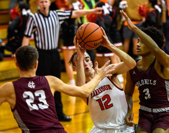 Harrison's Mason Bost (12) drives through defense from Henderson County's Xavier Bugg (23) and Daymian Dixon (3) as the Henderson County Colonels play the Evansville Harrison Warriors at Harrison Tuesday evening, January 7, 2020.