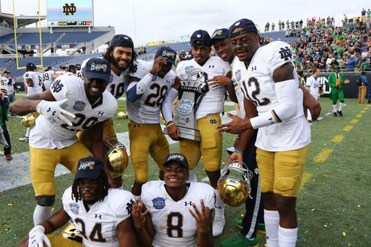 Dec 28, 2019; Orlando, Florida, USA;Notre Dame Fighting Irish defensive back Houston Griffith (3), defensive back DJ Brown (12),  cornerback Donte Vaughn (8)  and teammates celebrate after beating the Iowa State Cyclones at Camping World Stadium.