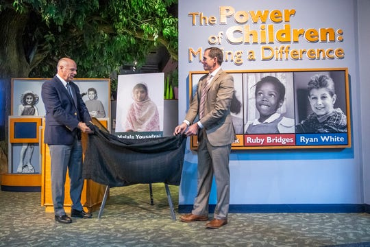 Dr. Jeff Patchen, president and CEO of the ChildrenÕs Museum of Indianapolis, and Mike Sherman, chairman of the board of the Children's Museum of Indianapolis, unveil the newest member of The Power of Children exhibit at the Children's Museum of Indianapolis, Malala Yousafzai, on Wednesday, Jan. 8, 2020.