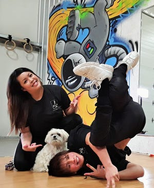 """Hip-hop dance enthusiasts Liz Baccam and Joel Sorenson are shown at their spacious North Liberty studio with their """"shop dog"""" named Zo. """"We're not in this for the profit,"""" they both stated."""