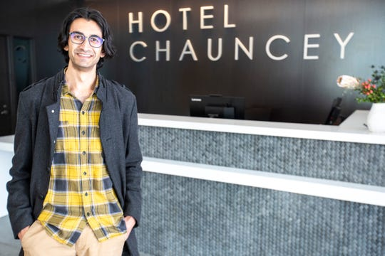 Raj Patel, chief development officer of Hawkeye Hotels, poses for a photo in front of the front desk, Wednesday, Jan. 8, 2020, at Hotel Chauncey in Iowa City, Iowa.